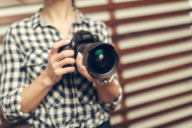 Jolie femme est un photographe professionnel avec appareil photo reflex numérique Photo Premium