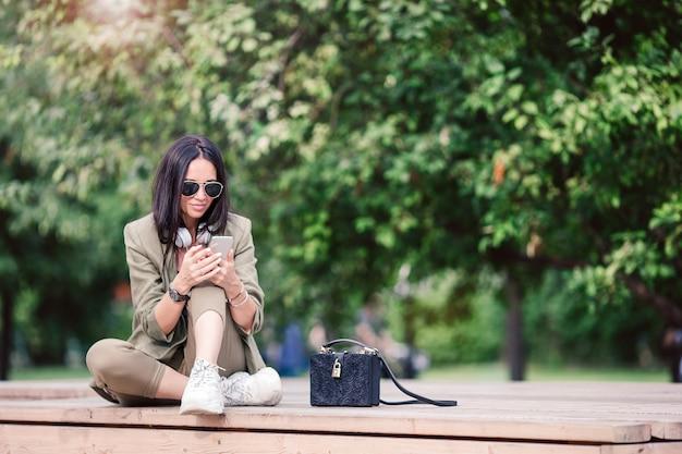 Jolie femme est en train de lire un sms sur un téléphone portable tout en restant assis dans le parc. Photo Premium
