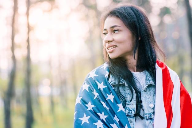 Jolie femme ethnique posant avec le drapeau des etats-unis Photo gratuit