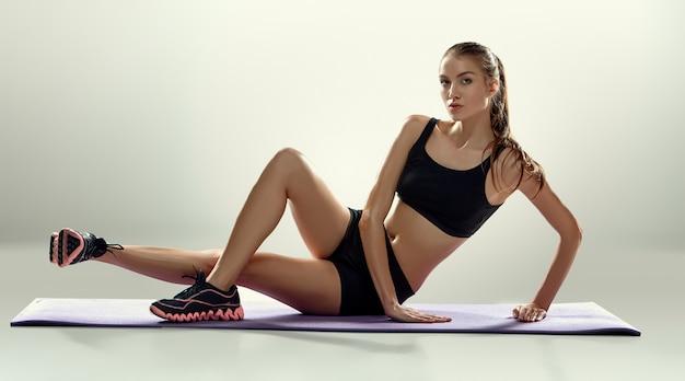 Jolie Femme Faire Des Exercices De Fitness Sur Un Tapis Lilas Photo gratuit