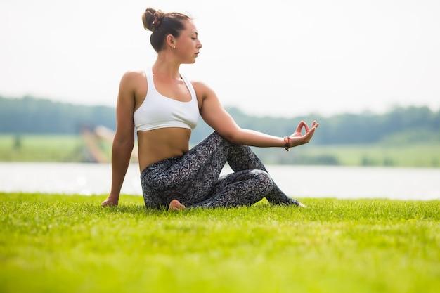 Jolie Femme Faisant Des Exercices De Yoga Dans Le Parc Verdoyant Photo gratuit