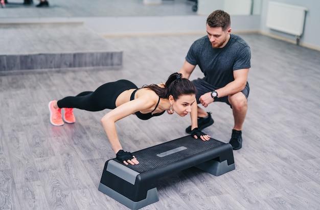 Jolie femme faisant des push-up avec l'aide d'un instructeur personnel isolé sur bois Photo Premium