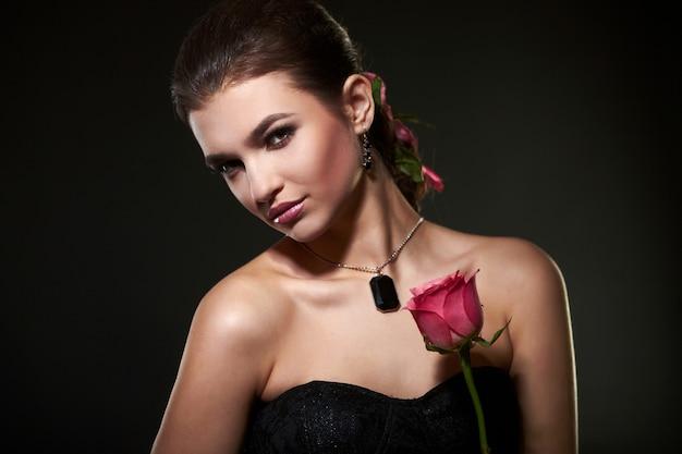 Jolie femme femme brune avec rose en studio Photo Premium