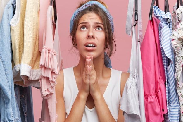 Jolie Femme Habillée Avec Désinvolture Debout Parmi Les Vêtements Suspendus Sur Une Grille Dans Sa Loge, Se Tenant La Main En Prière Photo gratuit