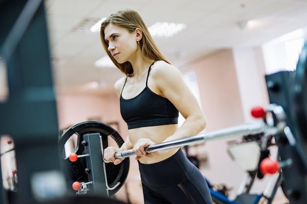 Jolie femme en haut noir et leggings est debout à la barre d'haltères dans la salle de gym. une sportive mince fait de l'exercice dans le centre de remise en forme et se tourne vers l'avenir. Photo Premium
