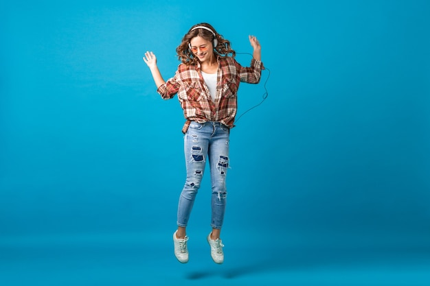 Jolie Femme Heureuse Sautant D'humeur Joyeuse En écoutant De La Musique Dans Les écouteurs En Chemise à Carreaux Et Jeans Isolés Sur Fond Bleu Studio Photo gratuit