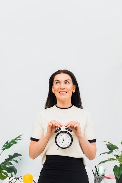 Jolie femme avec horloge dans les mains en souriant Photo gratuit
