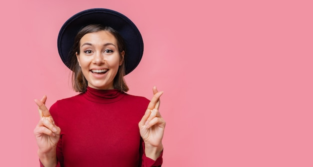 Jolie Femme Joyeuse Souhaite Faire De Son Mieux Pour Croiser Les Doigts, A Le Meilleur, Vêtue D'un Jamper Rouge Isolé. Gens, Concept De Langage Corporel. Photo gratuit