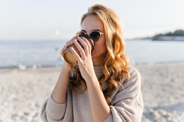 Jolie Femme En Lunettes De Soleil élégantes Au Repos Sur La Côte De La Mer. Portrait En Plein Air Du Modèle Féminin De Rêve Se Détendre Dans La Journée D'automne. Photo gratuit