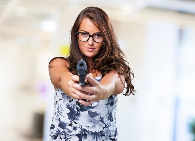 Jolie femme de la mafia tenant un fusil Photo gratuit
