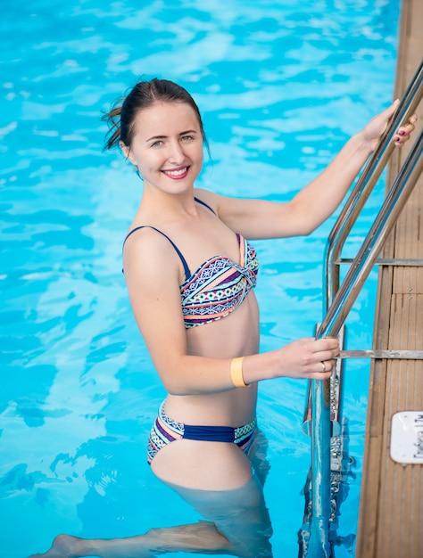 Jolie femme en maillot de bain va sortir de la piscine, regardant la caméra et souriant. beau fond d'eau turquoise Photo Premium
