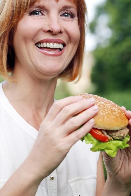 Jolie femme mangeant dans un parc Photo gratuit