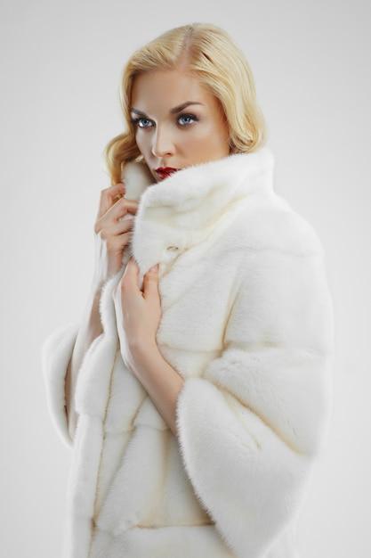 Jolie femme en manteau de fourrure blanche Photo Premium