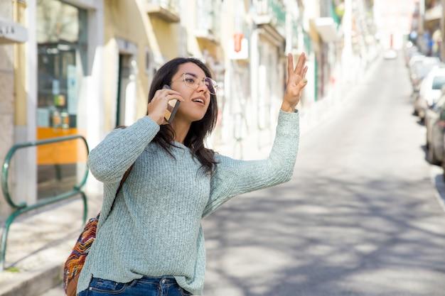 Jolie femme parlant au téléphone et appelant un taxi Photo gratuit