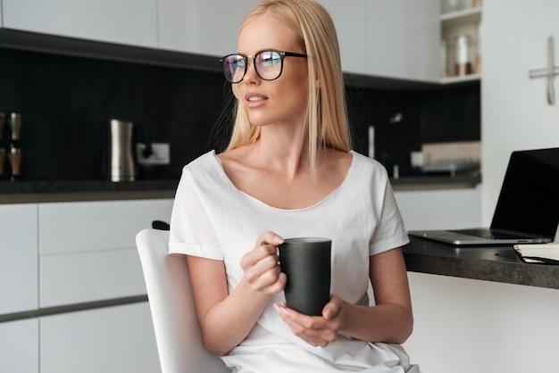 Jolie Femme Pensive Avec Tasse De Thé Assis Dans La Cuisine Photo gratuit