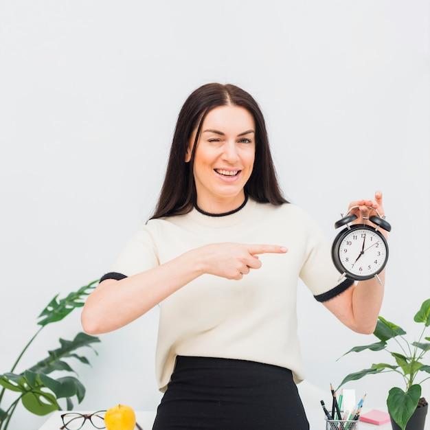 Jolie femme pointant son doigt sur l'horloge Photo gratuit