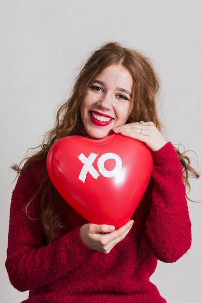 Jolie femme posant avec un ballon coeur Photo gratuit