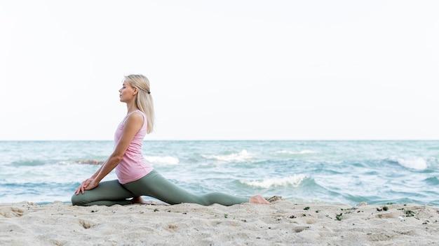 Jolie Femme Pratiquant Le Yoga à La Plage Photo gratuit