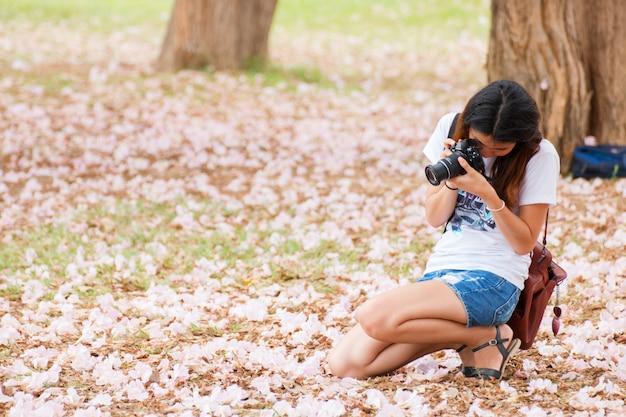 Jolie femme prenant une photo fleur rose Photo Premium