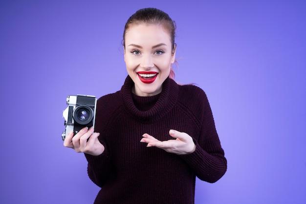 Jolie Femme En Pull En Tricot Nous Montre Son Nouvel Appareil Photo Photo gratuit
