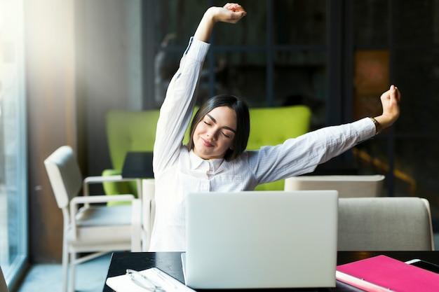 Jolie Femme Qui S'étend à L'ordinateur Portable Photo Premium