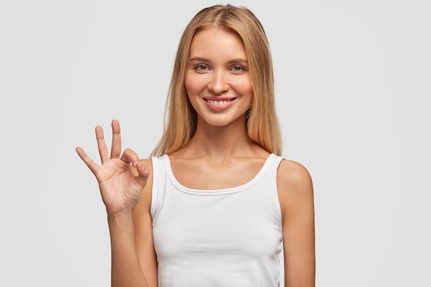 Jolie Femme De Race Blanche Aux Cheveux Longs, Expression Satisfaite, Montre Un Signe Correct, Se Sent Heureuse Après Avoir Rencontré Un Beau Mec, Isolé Sur Un Mur Blanc. Expressions Faciales Humaines, Langage Corporel Photo gratuit