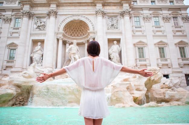 Jolie femme à la recherche de la fontaine de trevi lors de son voyage à rome, en italie. fille profiter de ses vacances en europe Photo Premium