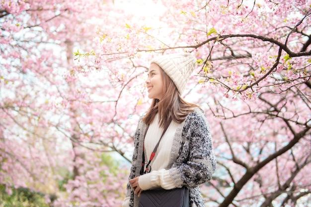 Jolie femme s'amuse avec des fleurs de cerisier à matsuda, japon Photo Premium