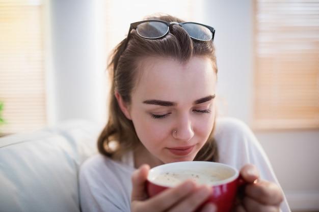 Jolie femme se détendre sur un canapé avec café dans le salon Photo Premium