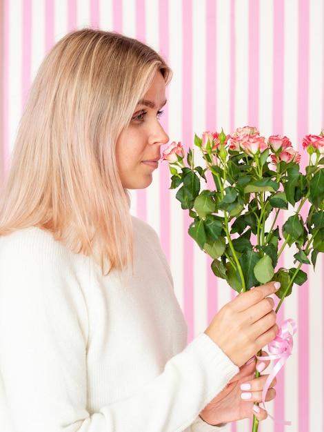 Jolie femme sentant le bouquet de fleurs Photo gratuit