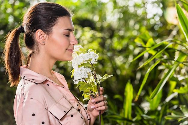 Jolie femme sentant les fleurs blanches Photo gratuit
