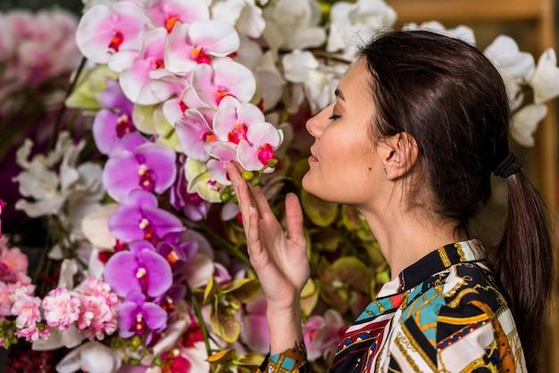 Jolie femme sentant les fleurs roses en serre Photo gratuit