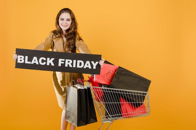 Jolie femme a signe vendredi noir avec panier rempli de sacs à provisions et de ruban de signalisation isolé sur jaune Photo Premium