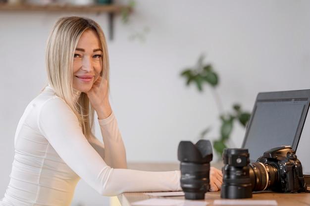 Jolie Femme à Son Espace De Travail Et Objectif De La Caméra Photo gratuit