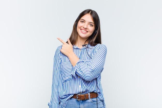 Jolie Femme Souriant Joyeusement, Se Sentant Heureuse Et Pointant Vers Le Côté Et Vers Le Haut, Montrant L'objet Dans L'espace De Copie Photo Premium