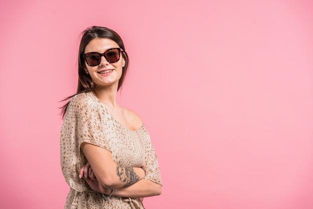 Jolie femme souriante à lunettes de soleil Photo gratuit