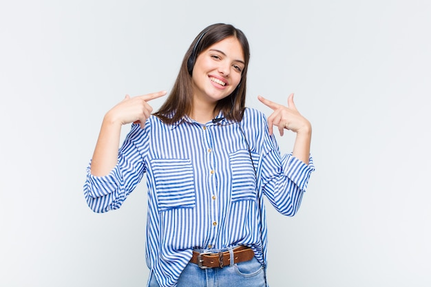 Jolie Femme Souriante Pointant Avec Confiance Vers Son Large Sourire, Attitude Positive, Détendue Et Satisfaite Photo Premium
