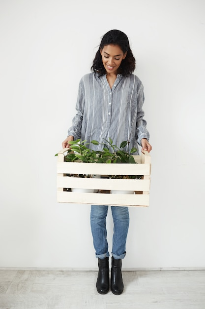 Jolie Femme Souriante Regardant Vers Le Bas Tenant Fort Avec Des Plantes En Pots De Fleurs Sur Mur Blanc Photo gratuit