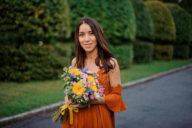 Jolie femme souriante en robe orange tenant un bouquet de fleurs Photo Premium