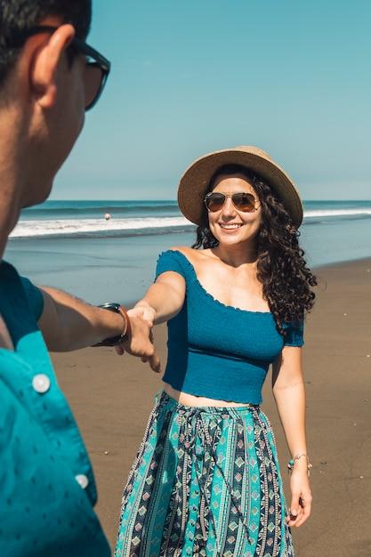 Jolie femme souriante tirant l'homme à la plage Photo gratuit