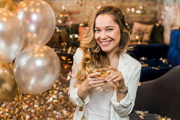 Jolie femme souriante avec un verre de whisky Photo gratuit