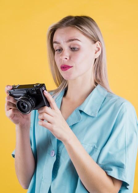 Jolie femme tenant caméra moyen coup Photo gratuit