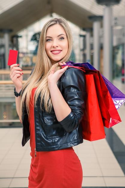 Jolie Femme Tenant Des Sacs à Provisions Et Montrant Une Carte De Crédit Vierge Photo gratuit