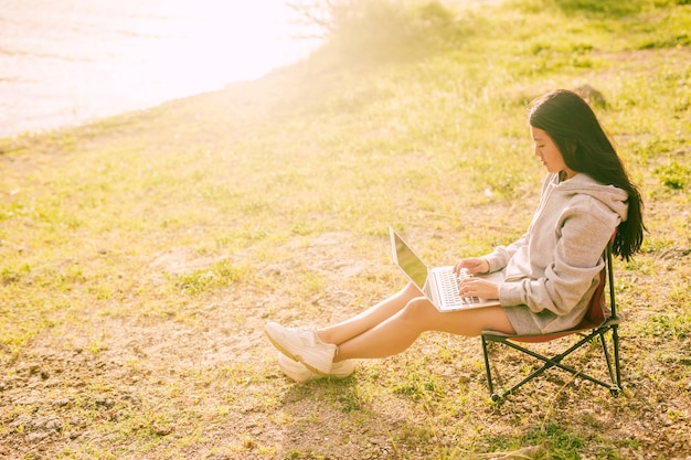 Jolie femme travaillant à distance à l'extérieur Photo gratuit