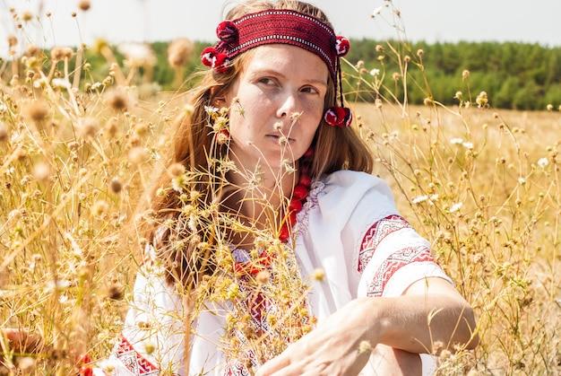 Jolie femme ukrainienne vêtue de vêtements brodés dans le champ Photo Premium