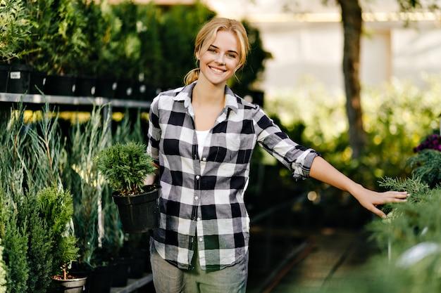 Jolie Femme En Vêtements Mignons Pour Atteindre Des Plantes En Serre Photo gratuit