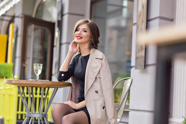Jolie Femme Vêtue D'une Robe Noire Et Trench Beige Avec Une Coiffure élégante Et Des Lèvres Rouges Sur Une Terrasse Photo gratuit