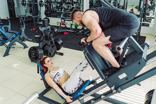 Une jolie femme vêtue de vêtements de sport blancs fait des exercices pour les jambes avec un homme sur un simulateur moderne dans la salle de sport. fille entre dans le sport avec un entraîneur personnel dans la salle de fitness. Photo Premium