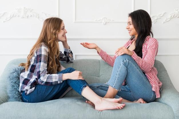 Jolie femmes discutant assis sur un canapé Photo gratuit