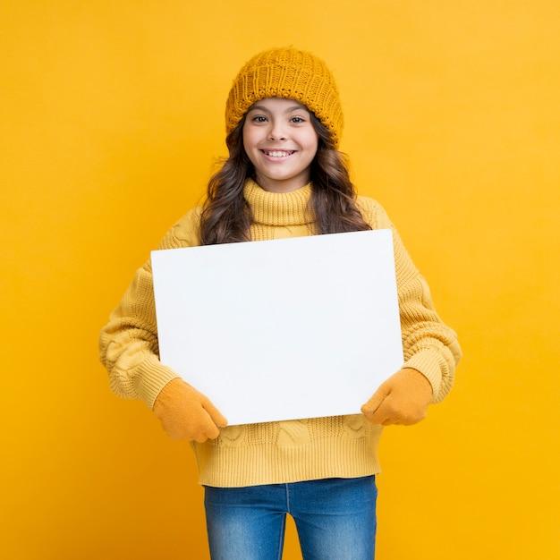 Jolie fille avec une affiche dans ses mains Photo gratuit